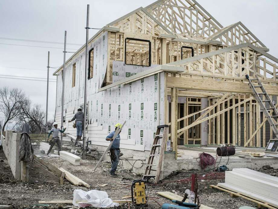 In January, construction workers put paneling on the side of a new home being built in the Carmona Hills neighborhood on the Southwest Side. Photo: Matthew Busch /For The San Antonio Express-News / © Matthew Busch