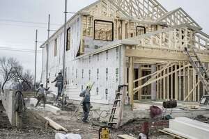 Construction workers David Flores, right, Areli Martinez, center, and Luis Ortigoza, left, put paneling on the side of a new house as homes are being built in the Carmona Hills neighborhood by KB Home on the Southwest Side of San Antonio. Construction hiring in Texas rose in August by 2,600 jobs.