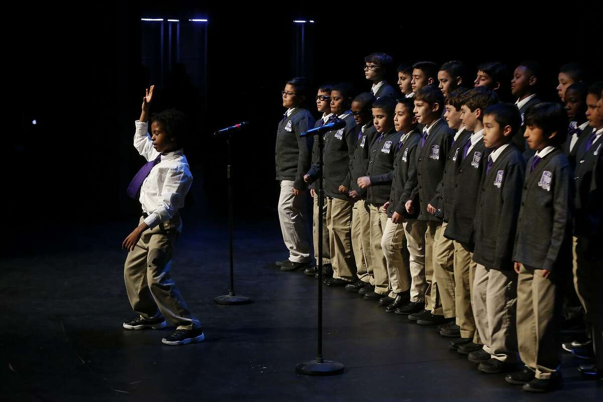 """Rico Carpenter leads members of the YMLA school choir as they perform their school song during """"Voices, Lift Every One,"""" a Dream Week event last year at Trinity University."""