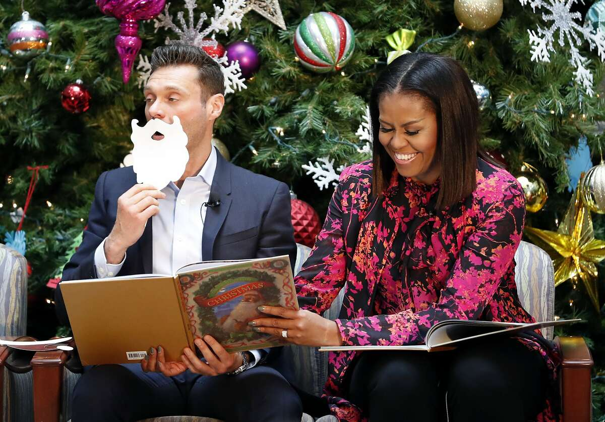 """FILE - In this Dec. 12, 2016 file photo, first lady Michelle Obama, accompanied by television and radio host Ryan Seacrest, reads """"Twas the Night Before Christmas,"""" during a holiday event at Children's National Health System in Washington. Obama toured the facility, visited with patients and families, read """"Twas the Night Before Christmas"""" to children and participated in a broadcast with Seacrest. (AP Photo/Alex Brandon, File)"""