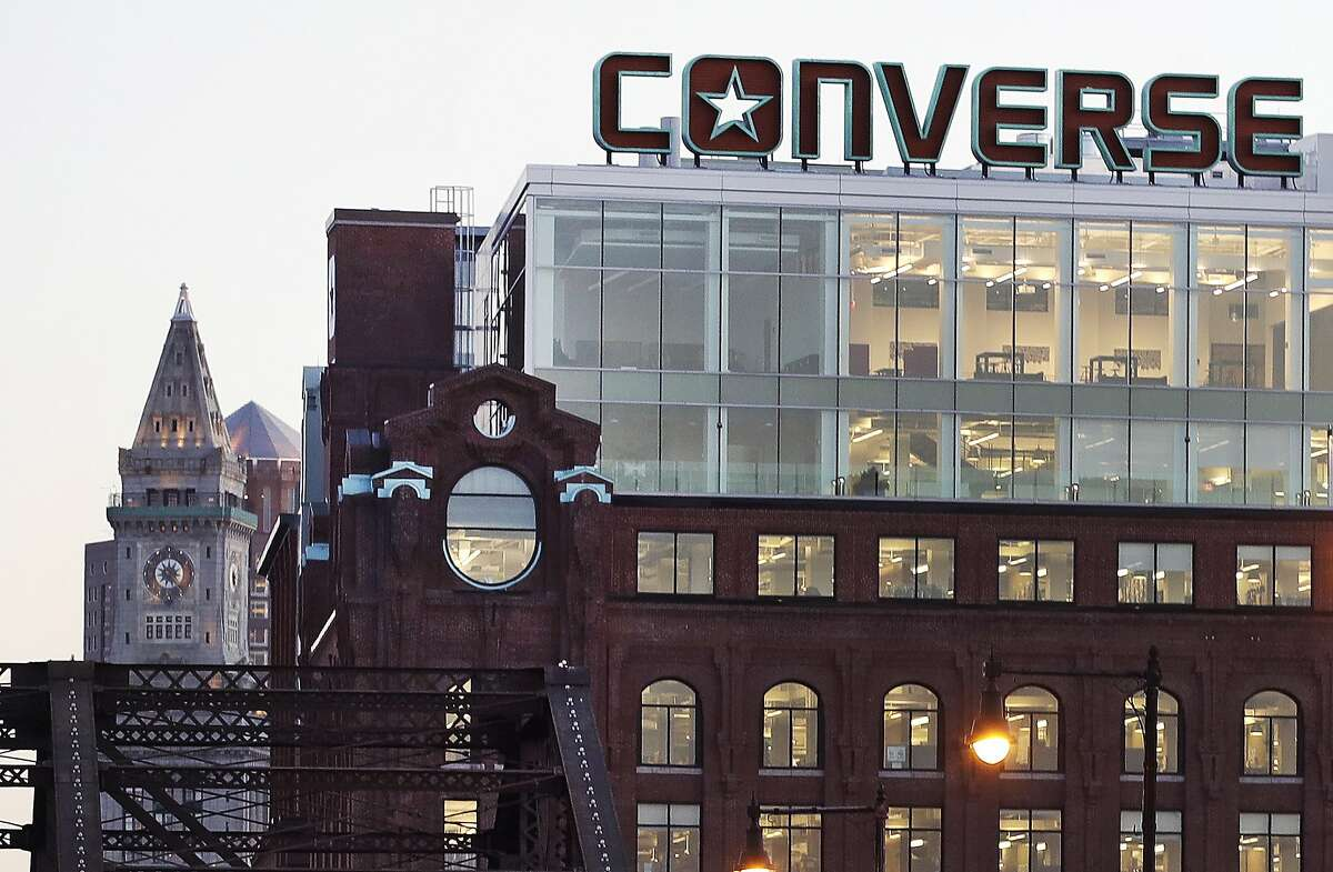 In this Wednesday, Dec. 28, 2016 photograph, the Converse logo is displayed on the roof of the company's world headquarters in the West End neighborhood of Boston. Some of America's top sneaker makers are racing to the Boston area. Reebok picked the city's Seaport District for its new global headquarters in December. Homegrown Boston-area companies New Balance and Converse opened new offices in 2015. At rear left is the historic Custom House Tower in Boston's Financial District. (AP Photo/Charles Krupa)