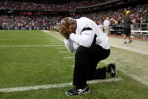 Coach Hue Jackson kneels on the field overcome with emotion after his Raiders beat the host Texans the day after Oakland owner Al Davis died in 2011.
