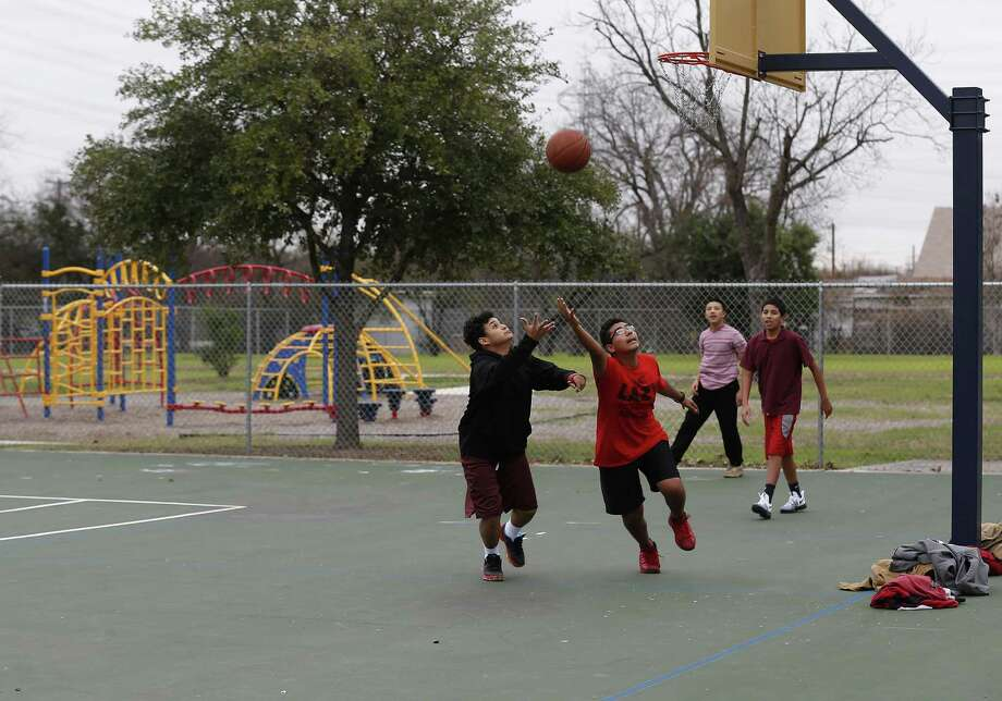 A group of kids play basketball as San Antonio Sports, working with the city and San Antonio Independent School District, opened its 17th school park at Wheatley Middle School on Wednesday, Jan. 4, 2017. Formerly called SPARKs, these parks are for kids during the day and open to the community for exercise and recreation after school and on weekends. They have playground equipment, walking trails and a soccer field. Exisiting sport courts also were resurfaced.(Kin Man Hui/San Antonio Express-News) Photo: Photos By Kin Man Hui / San Antonio Express-News / ©2017 San Antonio Express-News