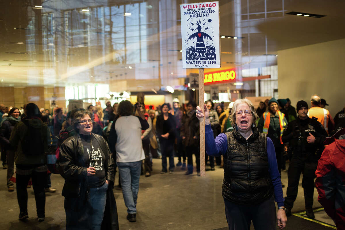 Dakota Access pipeline protesters fill the lobby outside the Wells Fargo Center in downtown Seattle on Thursday, Jan. 5, 2017. Several groups came together for a