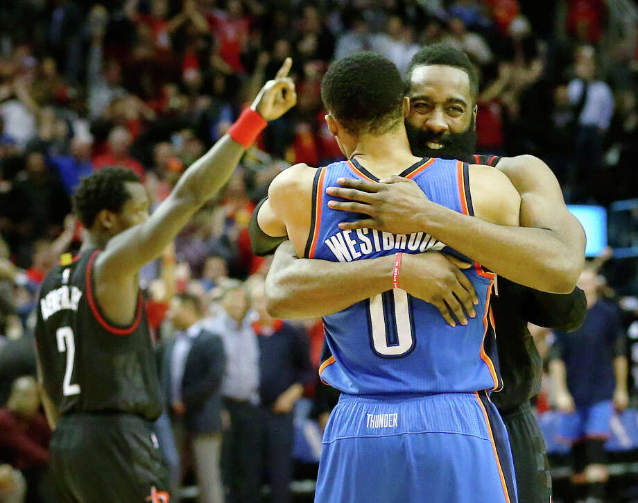 Rockets star James Harden, right, and his Thunder counterpart, Russell Westbrook, conclude Thursday night's game with a hug, while in the background Pat Beverley lets the Toyota Center crowd know which team won. Photo: Jon Shapley, Staff / © 2015  Houston Chronicle
