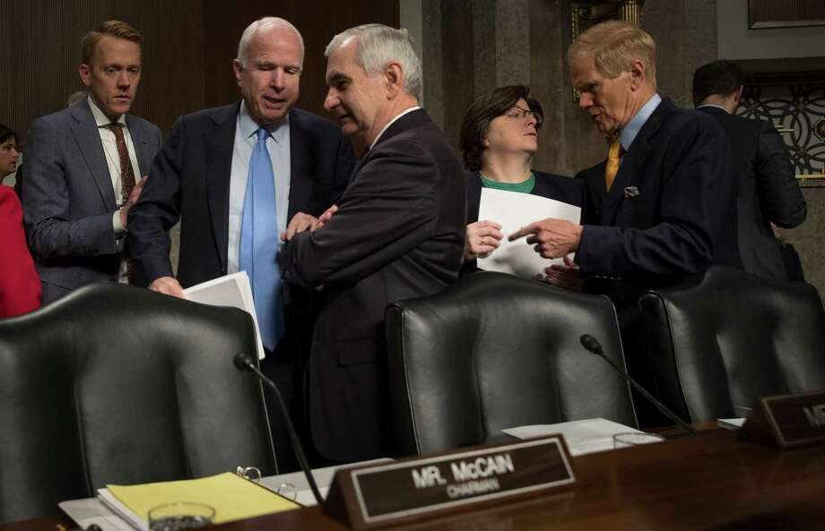 Sen. John McCain (R-Ariz.), second left, the committee chair, speaks with Sen. Jack Reed (D-R.I.) at a Senate Armed Services Committee hearing on foreign cybersecurity threats, on Capitol Hill in Washington, Jan. 5, 2017. McCain has called for a select committee to investigate Russian interference in the election. At right is Sen. Bill Nelson (D-Fla.) (Stephen Crowley/The New York Times) Photo: STEPHEN CROWLEY / NYTNS