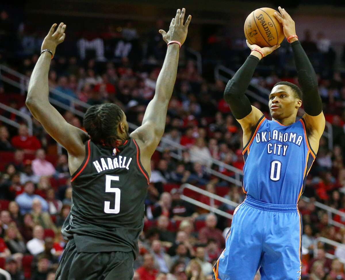 Oklahoma City Thunder guard Russell Westbrook (0) takes a three-point shot as Houston Rockets forward Montrezl Harrell (5) tries to block it during the fourth quarter of an NBA game at the Toyota Center, Thursday, Jan. 5, 2017, in Houston. ( Jon Shapley / Houston Chronicle )