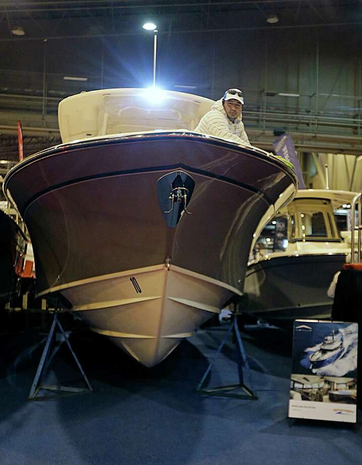 Malon Trigueros puts the finishing touches on a Grady White center console boat in the MarineMax booth during setup for The Houston International Boat, Sport & Travel Show Jan. 5, 2017, in Houston. ( James Nielsen / Houston Chronicle ) Photo: James Nielsen, Staff / © 2017  Houston Chronicle