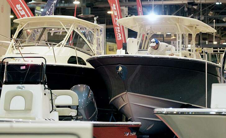 Malon Trigueros puts the finishing touches on a Grady White center console boat in the MarineMax booth during setup for The Houston International Boat, Sport & Travel Show Jan. 5, 2017, in Houston. ( James Nielsen / Houston Chronicle )