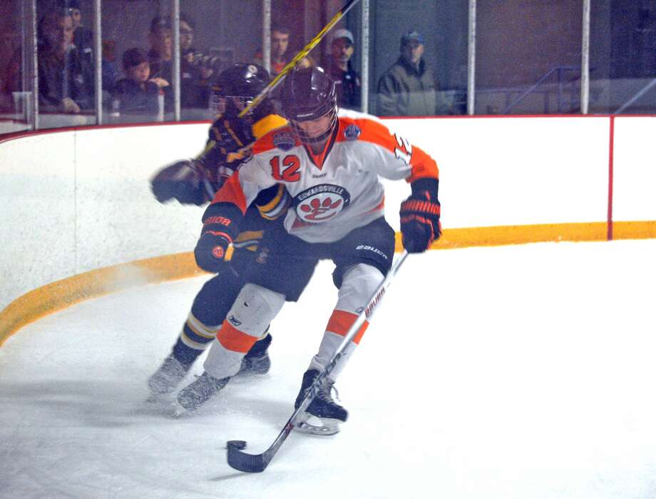 Edwardsville's Stanley Lucas, right, battles an Oakville defender for the puck during Thursday's game at the East Alton Ice Arena.