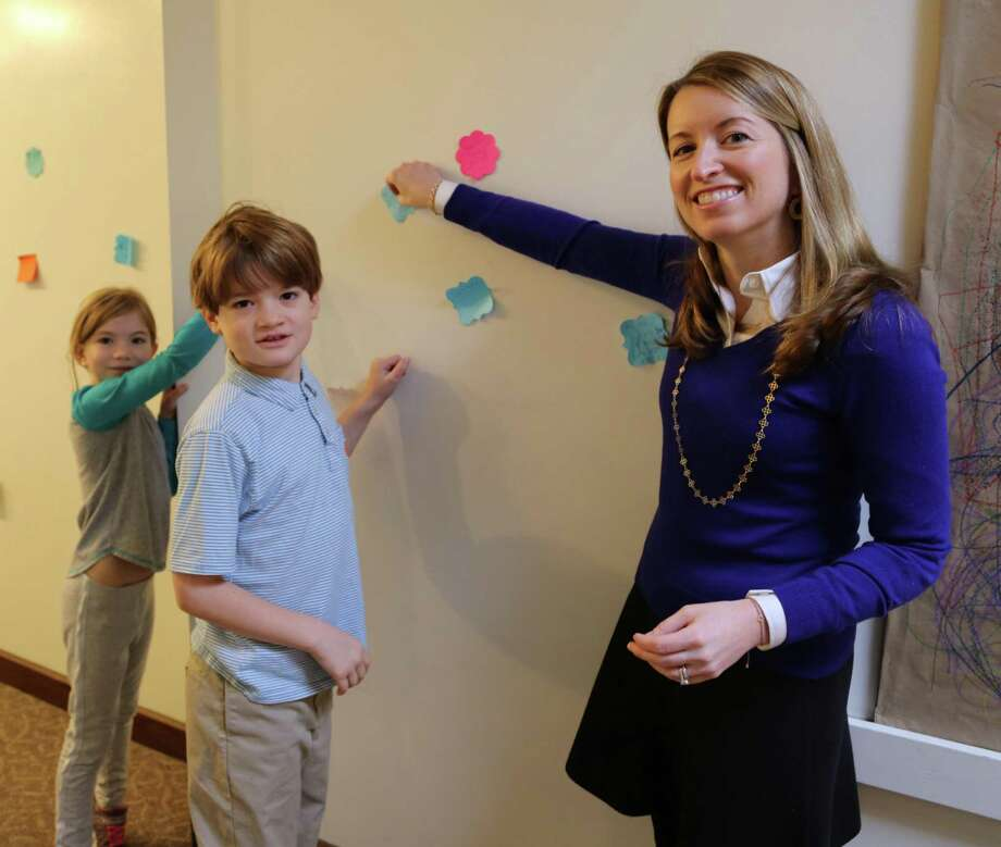 Lillian Back of Norwalk, Harry Jellinek of Darien and Head of Lower School Meaghan Mallin of New Canaan post sticky notes detailing acts of kindness they spotted at the New Canaan Country School in December. Photo: Contributed Photo / New Canaan News