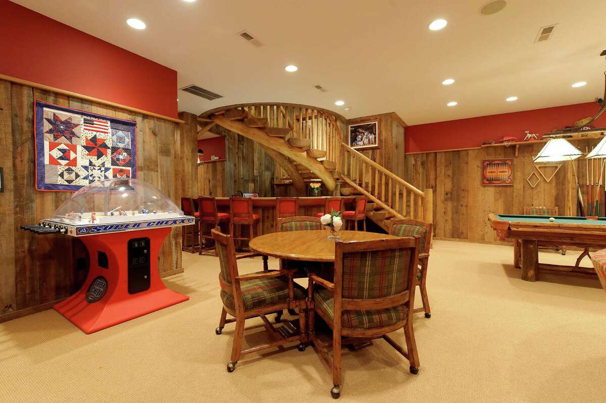 The sports barn features a large game room, a full service bar, and a sculptural staircase.