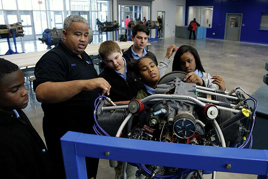 Marvin Smith III 2nd from left, discusses an aircraft engine during his 9th grade Aviation History class in the aviation hanger at HISD's Sterling Aviation High School  Jan. 4, 2017, in Houston. Photo: James Nielsen, Houston Chronicle / © 2017  Houston Chronicle
