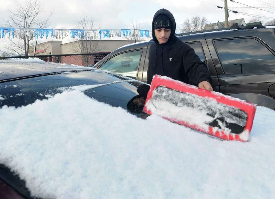 Omar Alwani cleans off the cars at West End Auto in Bridgeport, Conn. after a small amount of snow fell on the area on Friday, Jan. 6, 2017 Photo: Cathy Zuraw / Hearst Connecticut Media / Connecticut Post
