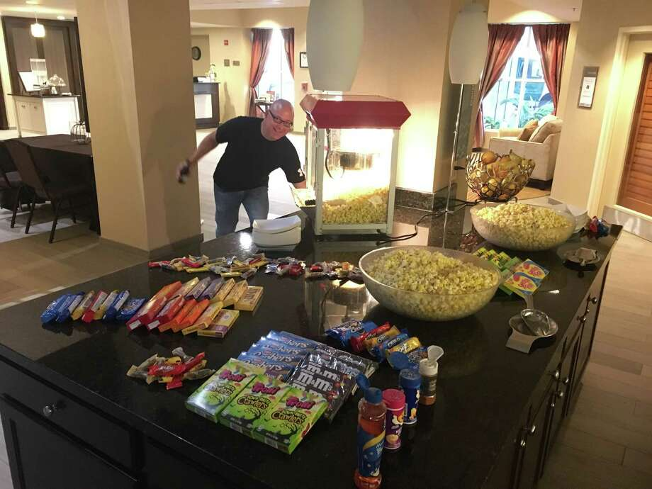 Mark Linabury with ServiceMaster poses next to complimentary popcorn and candy at the movie night event benefiting Mission Northeast hosted by Homewood Suites in Kingwood in October 2016. Photo: Courtesy Of Homewood Suites In Kingwood