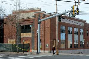 Work crews have begun replacing windows on the former Black Rock Bank & Trust structure at the corner of Fairfield Avenue and Brewster Street in Bridgeport, Conn. The property has been vacant since the Black Rock Arts Center was forced out in 2009.