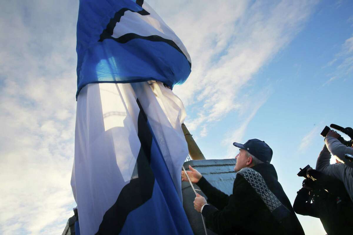 Former Seahawks quarterback Dave Kreig raises the 12s flag over the Space Needle, Friday morning, in advance of Saturday's Seahawks playoff game against Detroit.