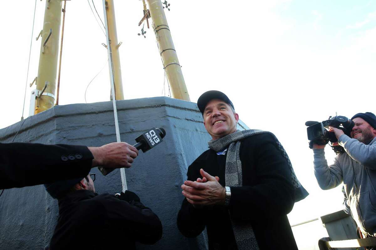 Former Seahawks quarterback Dave Kreig smiles after raising the 12s flag over the Space Needle, Friday morning, in advance of Saturday's Seahawks playoff game against Detroit.