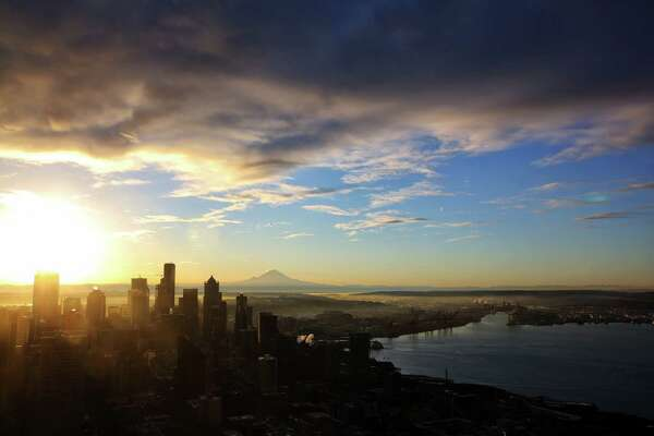 The sun rises over Mount Rainier and the Seattle skyline early Friday morning as seen from the Space Needle.