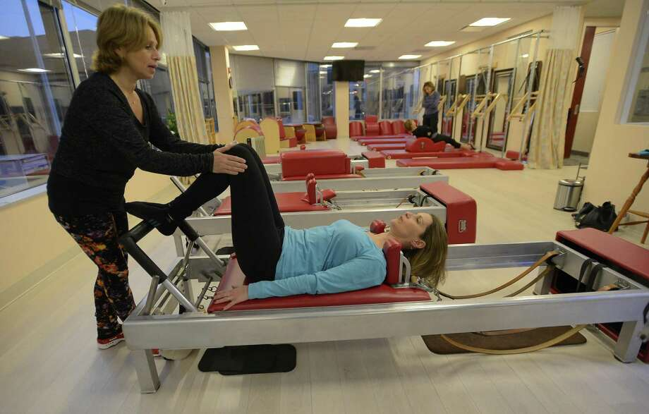 Simona Cipriani, a second generation Pilates instructor, who owns the Art of Control Pilates studio, works with Doreen Rakowsky, of New Fairfield, in the Art of Control studio in the Synergy Health and Fitness center of Stamford, on Jan. 3, 2016. Photo: Matthew Brown / Hearst Connecticut Media / Stamford Advocate