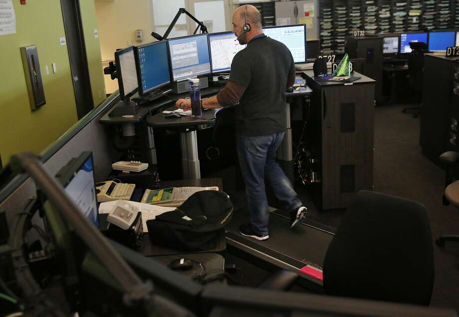 Ron Davis takes calls while walking on a treadmill and working overtime hours at the 911 dispatch center in January. Photo: Leah Millis, The Chronicle