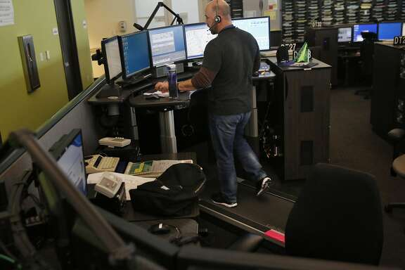 Ron Davis takes calls while walking on a treadmill and working overtime hours at the 911 dispatch center Jan. 6, 2017 in San Francisco, Calif.