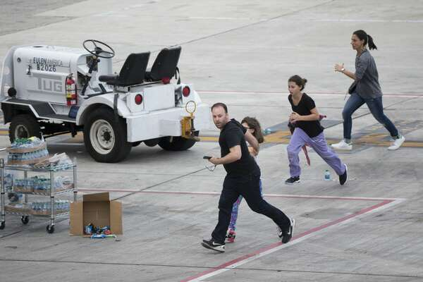 People run on the tarmac at Fort Lauderdale–Hollywood International Airport, Friday, Jan. 6, 2017, in Fort Lauderdale, Fla., after a shooter opened fire inside a terminal of the airport, killing several people and wounding others before being taken into custody. (AP Photo/Wilfredo Lee)