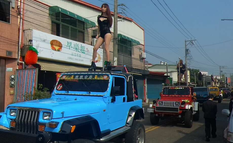 This picture taken on January 3, 2017 shows pole dancers performing on top of jeeps during the funeral procession of former Chiayi City county council speaker Tung Hsiang in Chiayi City, southern Taiwan. Fifty pole dancers clad in black bikinis gave one Taiwan politician a raucous final send-off in an eyebrow-raising funeral parade that jammed traffic and drew crowds of onlookers. Photo: STR/AFP/Getty Images