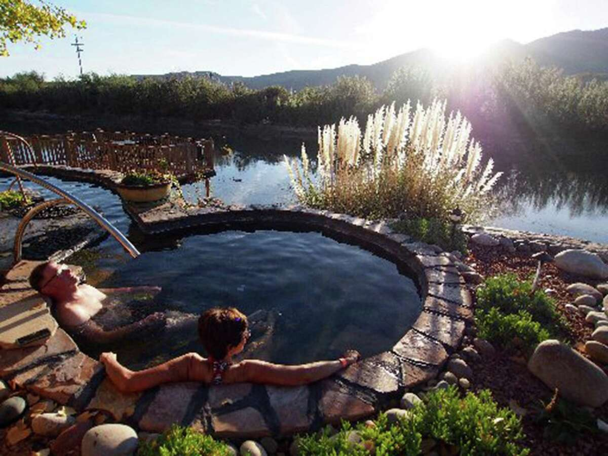 Carol and Don Baumgardt look across the Rio Grande during an early morning soak at Riverbend Hot Springs in the small town of Truth or Consequences, N.M.