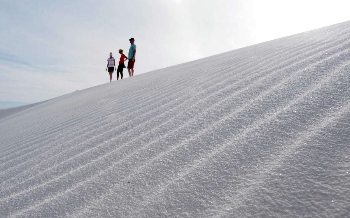 Gretch Sanders, Carol Baumgardt and Don Baumgardt walk along a sand dune at White Sands National Monument in New Mexico.