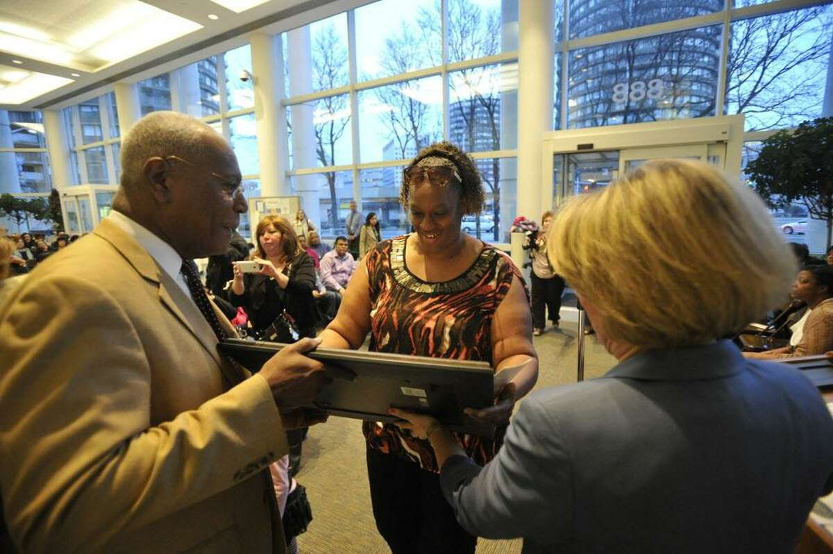 FILE - Pamela Dais, center, is given her diploma by Phillip McKain, left, and Patti Keckeisen during the Parent Leadership Training Institute's graduation ceremony in the lobby of the Stamford Government Center on Thursday, April 4, 2013.
