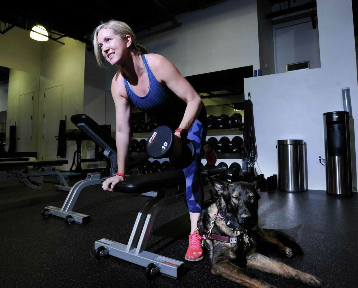 With her German Shepherd service dog Woodstock by her side, Greenwich resident Amy Dixon, a triathlete who is blind, works out at Combine Training in Greenwich. Dixon will soon be running a camp for blind triathletes later this month in California.