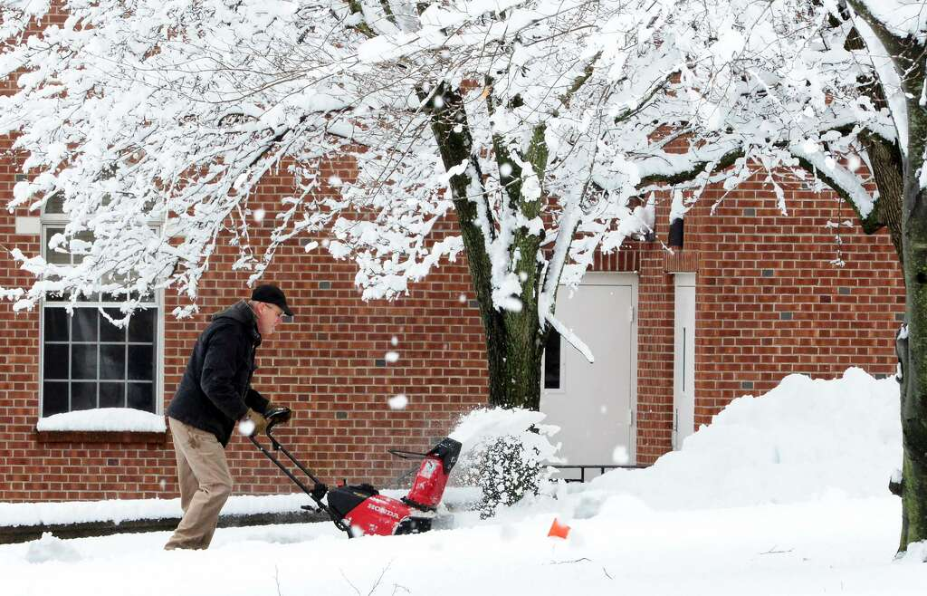 Mark Bernier Uses A Snowblower To Clear An Area At The River Park Apartments After An
