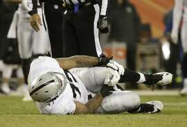 Oakland Raiders tackle Donald Penn lies on the turf with an injury in the second half of an NFL football game against the Denver Broncos, Sunday, Jan. 1, 2017, in Denver. (AP Photo/Jack Dempsey)