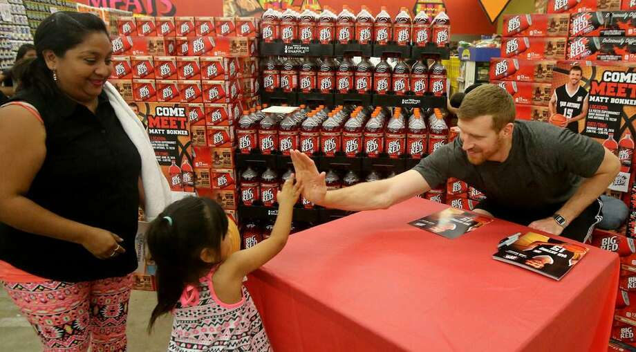 San Antonio Spurs forward Matt Bonner (right) exchanges high fives with Espernaza Hernandez,4, before signing an autograph on June 20, 2016 at the La Fiesta Supermarket on Ingram Road. Bonner was there to mingle with fans, sign autographs and promote Big Red soda. On the far left is Esperanza's mom Maria. Photo: File Photo /San Antonio Express-News