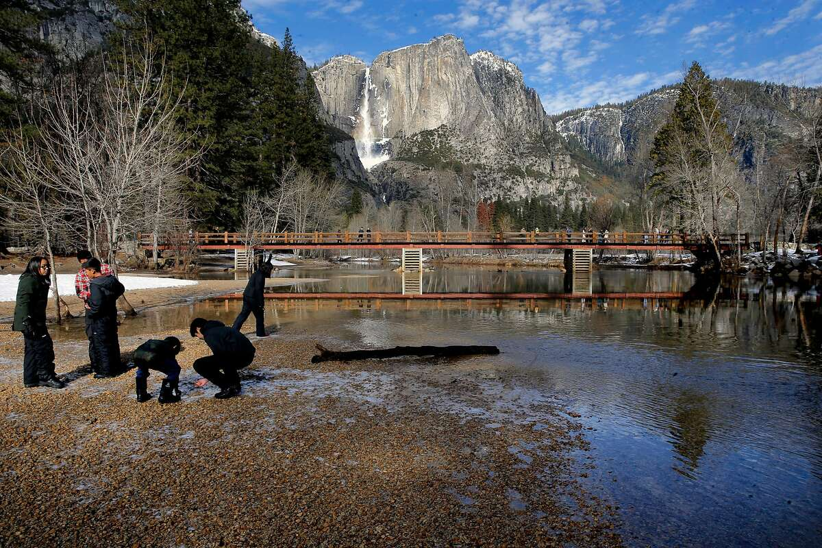 Visitors play along the Merced River in Yosemite National Park on Friday Jan. 6, 2017, where weather forecasters are expecting a huge storm to hit the valley over the next three days.