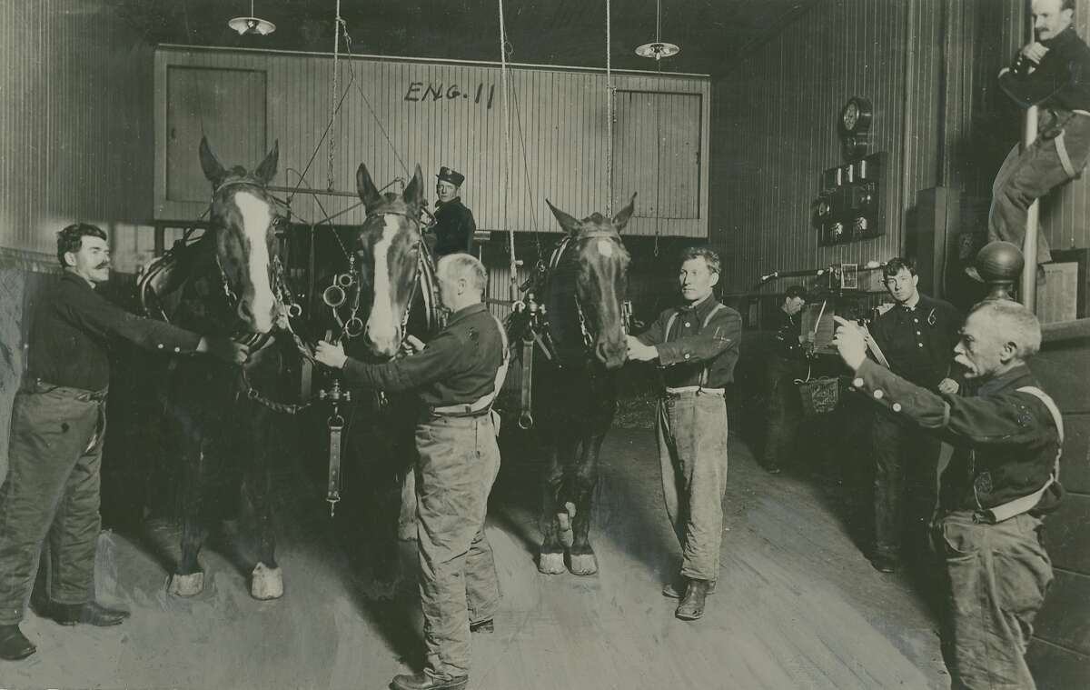 """This old photo was used for an article that was dated June 18, 1939. It is an early photo from the 1890's. The caption on the back read: How They Did It in the """"Gay Nineties."""" It is a far cry today from this scene, photographed in the days when horses still dragged our fire engines through the streets. Here is shown firemen of No. 11 Engine responding to an alarm. Some are descending by the """"monkey poles,"""" while others have already reached the horses, who have backed into position under the hanging harness by themselves as they were trained to do. Horse-drawn apparatus could be harnessed and driven to the curb in less than half a minute in the old days."""
