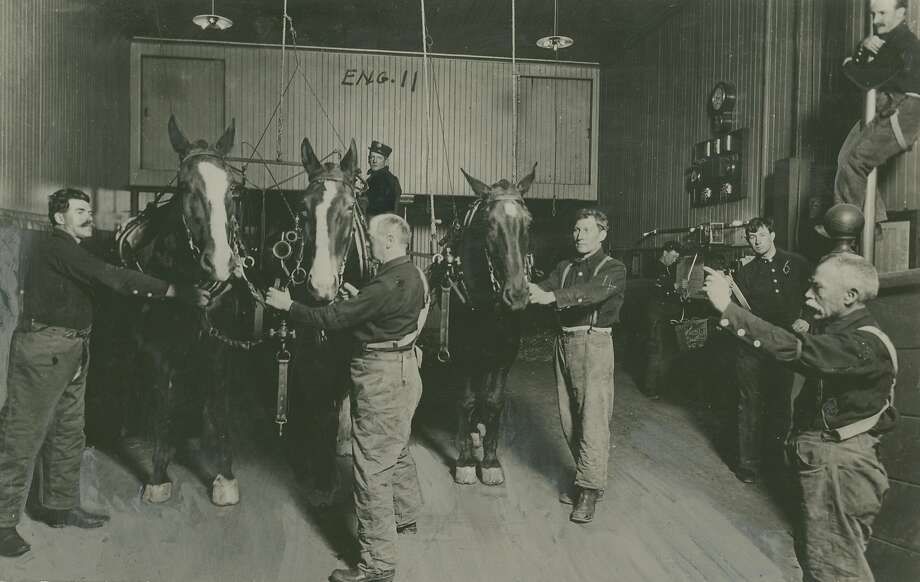 "This old photo was used for an article that was dated June 18, 1939. It is an early photo from the 1890's. The caption on the back read:  How They Did It in the ""Gay Nineties."" It is a far cry today from this scene, photographed in the days when horses still dragged our fire engines through the  streets. Here is shown firemen of No. 11 Engine responding to an alarm. Some are descending by the ""monkey poles,"" while others have already reached the horses, who have backed into position under the hanging harness by themselves as they were trained to do. Horse-drawn apparatus could be harnessed and driven to the curb in less than half a minute in the old days. Photo: Chronicle Archives"