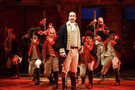 "FILE - In this file photo released by The Public Theater, Lin-Manuel Miranda, foreground, performs with members of the cast of the musical ""Hamilton"" in New York. A group dedicated to studying Alexander Hamilton will gather Thursday, July 7, 2016, in New Jersey. One of the researchers, Michael Newton, says that he has traced the story that Martha Washington named her feral tomcat after Hamilton to a piece of satire written by a man described as a British captain. The tale is included in a song in the hit Broadway show ""Hamilton"" and in the biography that it's based on. (Joan Marcus/The Public Theater via AP, File) MANDATORY CREDIT"