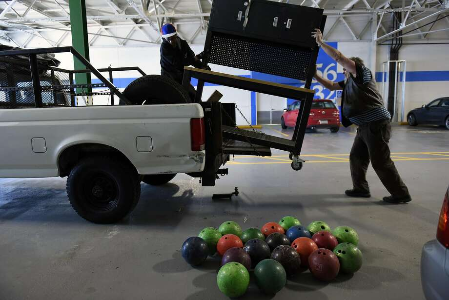 Artist Steve Heck, right, and friend Paul Casteel, lift a cabinet onto Heck's truck as he moves his studio out of a shared space at The Factory 510, a co-working space in San Leandro. Heck had hoped to turn the nearby pile of bowling balls into an art project. Photo: Michael Short, Special To The Chronicle