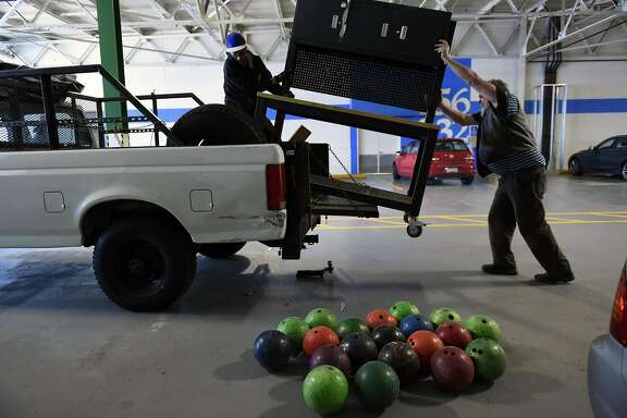A pile of bowling balls are seen as artist Steve Heck, right, and friend Paul Casteel, lift a cabinet onto Steve's truck as he moves his studio out of a shared space at The Gate 510, a co-working space in San Leandro, CA, on Thursday, January 5, 2017.