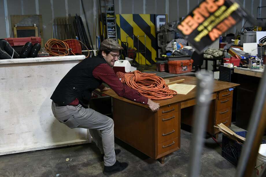Tyler Kobick, of Design Draw Build, moves a desk as he prepares to move out of the space he shares with others at The Factory 510, a co-working space in San Leandro. Photo: Michael Short, Special To The Chronicle