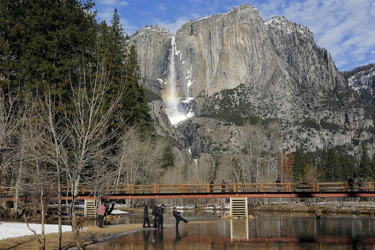 Visitors play along the Merced River with Yosemite Falls in the Yosemite National Park on Friday Jan. 6, 2017, where weather forecasters are expecting a huge storm to hit the valley over the next three days.