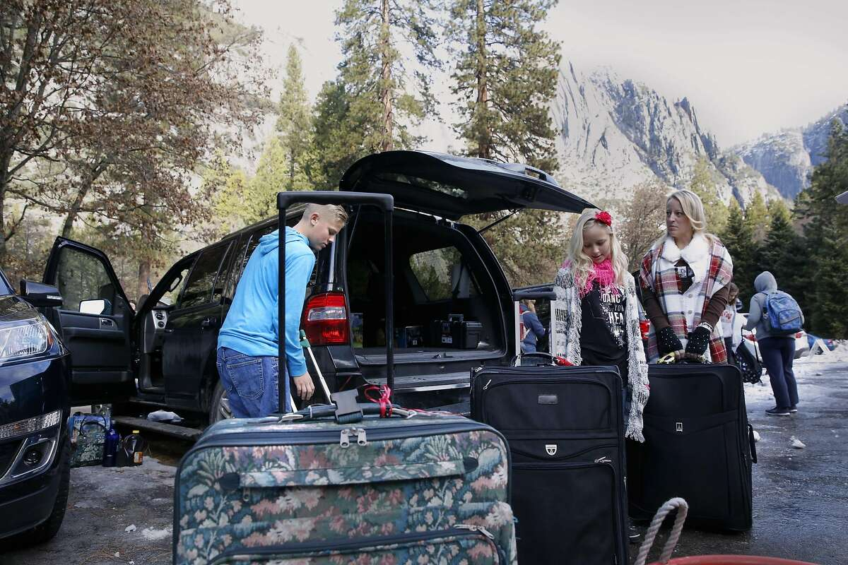 Chris Guyot, 13, Kayleigh, 10 and their mom Tricia and the rest of the family Evan Guyot and Tyler, 19, (not pictured) of Orange, Ca. pack up their belongings after being told to evacuate the Yosemite Valley Lodge, in Yosemite National Park on Friday Jan. 6, 2017, where weather forecasters are expecting a huge storm to hit the valley over the next three days.