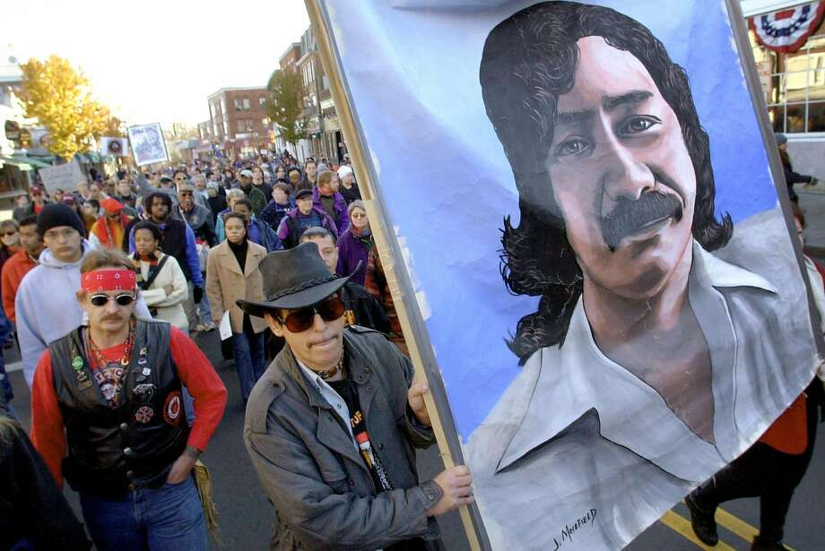 Marchers carry a large painting of Leonard Peltier in Plymouth, Mass., during a National Day of Mourning in November 2001. Photo: STEVEN SENNE, ASSOCIATED PRESS