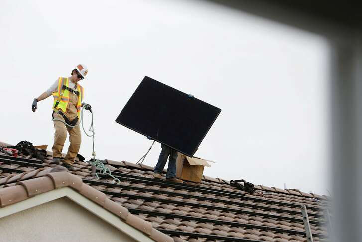 Elite Electric installer Kevin Kinney (left) navigates a roof as an Elite Electric installer carries a SunPower solar panel while installing it on  a roof at a new home being constructed at a Mertiage Home's community called Kingston Square on Friday, January 6,  2017 in Hayward, Calif.