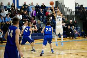 BRITTNEY LOHMILLER   blohmiller@mdn.net Meridian's Lucas Lueder shoots for three points in the first half of the Friday evening game against Gladwin.