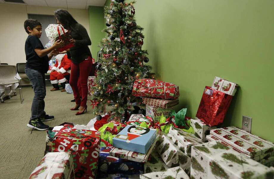 Herlinda Ramos and her grandson, Donovan Leos, 9, help hand out presents during a Christmas party at the Bexar County Juvenile Probation Center on Wednesday, Dec. 7, 2016. The center's Volunteers In Probation (VIP) Program has fostered trusting relationships with juvenile offenders for over 30 years. The volunteers are the backbone of the program but despite the success mentors are in short supply. For Christmas celebrations, the center received gifts and support for a meal from USAA for families who have a young member going through the county's probation program. A gathering took place where pizza and cake were consumed and finally gifts were given out to the children.  (Kin Man Hui/San Antonio Express-News) Photo: Kin Man Hui, Staff / San Antonio Express-News / ©2016 San Antonio Express-News