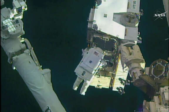 In this still image taken from video provided by NASA, astronaut Peggy Whitson takes a spacewalk outside the International Space Station on Friday, Jan. 6, 2016.  Whitson and Commander Shane Kimbrough went spacewalking  to hook up fancy new batteries on the International Space Station's sprawling power grid. (NASA via AP)