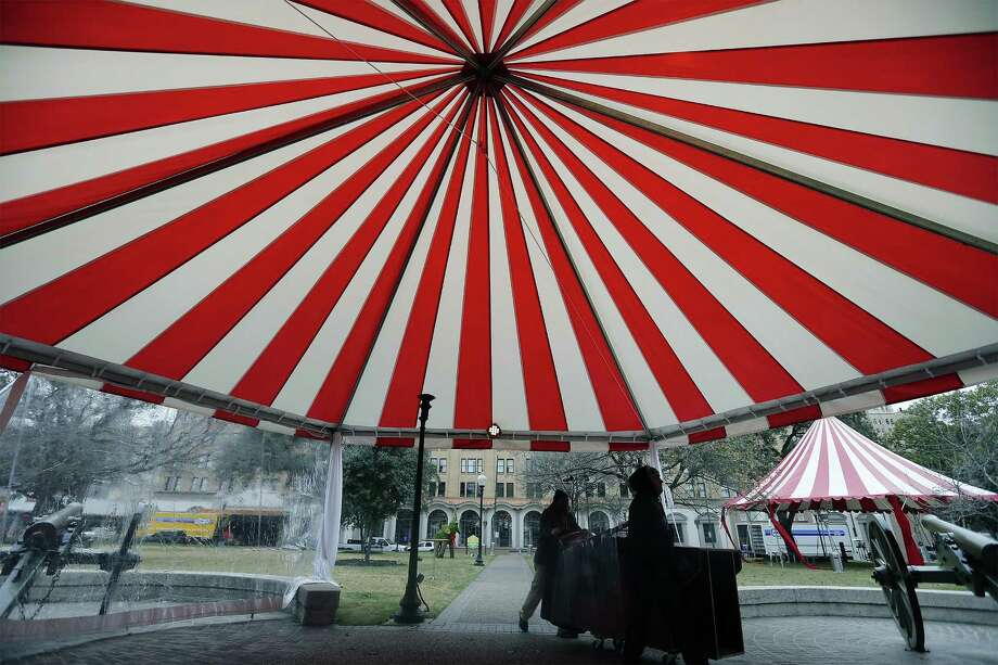 """Work crews continuing staging for party at Travis Park on Friday, Jan. 6, 2017. Large red-and-white-striped tents have replaced Travis Park's holiday scenery ahead of a massive bash to be hosted on the park grounds and its neighbor, the elegant St. Anthony Hotel, Saturday. Elizabeth and Barry Roberts, of Terrell Hills, are hosting the party and have rented out the entire park and a large portion of the historic hotel. The park is closing to the public beginning Friday for an anticipated 1,200 guests of the Roberts, who will enjoy attractions like a carousel, Ferris Wheel, jugglers, musical performances and permitted animals including: two camels, two zebras and """"some smaller animals,"""" according to the city of San Antonio. Asst. city manager Lori Houston says the company that is organizing the event has paid about $18,800 for the park-use permit and $11,000 for street closure and right of way use. The funds will be invested back into the park.(Kin Man Hui/San Antonio Express-News) Photo: Kin Man Hui, Staff / San Antonio Express-News / ©2017 San Antonio Express-News"""